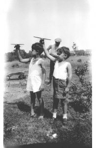 """Bill and Howard """"flying"""" model airplanes while Dad raked the yard."""